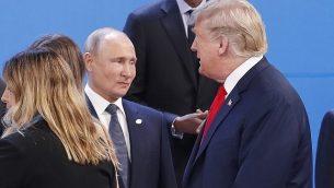 الرئيس الأمريكي دونالد ترامب يمر من أمام الرئيس الروسي فلاديمير بوتين، من اليسار، خلال الاستعداد لالتقاط صورة جماعية في افتتاح فعالية قمة ال20 في بوينوس آيرس، الأرجنتين، 30 نوفمبر، 2018.  (AP Photo/Pablo Martinez Monsivais)