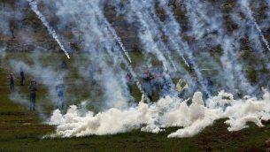 قوات إسرائيليى تطلق غازا مسيلا للدموع على متظاهرين فلسطينيين خلال مواجهات في قرية المغير بالقرب من رام الله، بعد تشييع جثمان حمدي نعسان، 27 يناير 2019 (AP Photo/Majdi Mohammed)