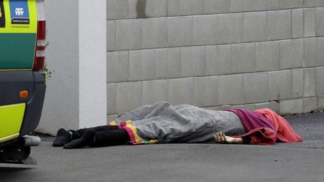 جثة ملقاة على الأرض خارج مسجد في وسط مدينة كرايست تشيرتش النيوزيلندية، الجمعة، 15 مارس، 2019. شهود عيان يقولون إن عددا كبيرا من الأشخاص قُتلوا في إطلاق نار استهدف مسجدين في المدينة. (AP Photo/Mark Baker)
