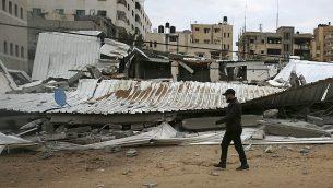 فلسطيني يتفقد الأضرار في وزارة شؤون الأسرى التابعة لحماس بعد غارة جوية إسرائيلية، مدينة غزة، 15 مارس، 2019.  (AP Photo/Adel Hana)