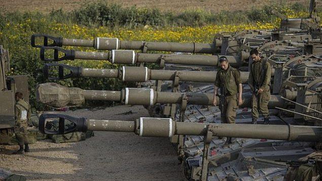 جنود إسرائيليون يجلسون فوق مدفعية متحركة بالقرب من الحدود مع قطاع غزة، في جنوب إسرائيل، 27 مارس، 2019. (AP Photo/Tsafrir Abayov)