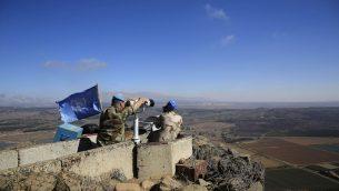 عناصر قوات حفظ السلام للأمم المتحدة يراقبون محافظة القنيطرة السورية من نقطة مراقبة في الطرف الإسرائيلي من مرتفعات الجولان، 16 سبتمبر 2014 (AP Photo/Tsafrir Abayov)