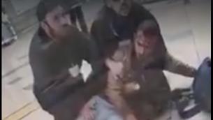 جندي اسرائيلي يمسكه حارسين امنيين في محطة قطار في بئر السبع، بعد ان ضربه الحراس لرفضه المفترض اظهار بطاقة هويته، 3 مارس 2019 (Screen capture: Facebook)
