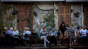 يجلس رواد في مطعم في شارع روتشيلد في تل أبيب، في 22 يونيو 2017 (Miriam Alster / FLASH90)