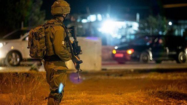توضيحية: جنود إسرائيليون يقفون بالقرب من موقع ما يُشتبه بأنه هجوم دهس عند مدخل قرية حوسان، في الضفة الغربية، 23 يونيو، 2018. (Flash90)
