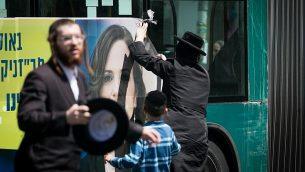 محتجون حريديم يقومون بتشويه ملصق إعلاني للمرشحة لرئاسة بلدية القدس، راحيل عزاريا، في حي 'مئة شعاريم' في الميدنة، 26 يوليو، 2018.  (Yonatan Sindel/Flash90)