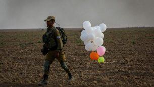 توضيحية: جندي إسرائيلي يقف بجانب بالونات أطلقها متظاهرون فلسطينيون من قطاع غزة وهبطت داخل إسرائيل في 19 أكتوبر، 2018. (Yossi Zamir/Flash90)