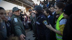 """تساعد نساء حرس الحدود أعضاء حركة """"نساء الحائط"""" في الخروج بعد محاولة عقد صلاة شهرية، حيث إحتج آلاف النساء والرجال المتشددين عند حائط المبكى في القدس القديمة، 8 مارس / آذار 2019. (Hadas Parush/Flash90)"""