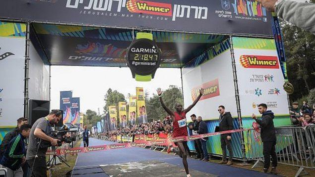 رونالد كيملي (33 عاما)، من كينيا، يجتاز خط النهاية في ماراثون القدس الدولي 2019 بتوقيت 02:18:47، 15 مارس، 2019. (Noam Revkin Fenton/Flash90)