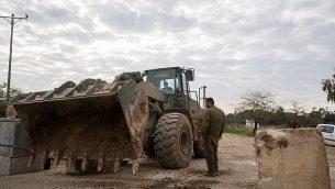 جنود الجيش الإسرائيلي يقفون بجانب جرافة عسكرية وهم يحرّكون المتاريس الإسمنتية لفتح طريق أغلقه الجيش قبل يوم واحد بالقرب من حدود غزة، في 26 مارس / آذار 2018. (Yonatan Sindel / Flash90)