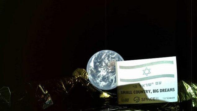 """صورة تم التقاطها من المركبة الفضائية 'بيريشيت' يظهر فيها العلم الإسرائيلية على لافتة مع عبارتي """"عام يسرائيل حاي"""" أو """"شعب إسرائيل حي""""، وبالانجليزية """"بلد صغير، أحلام كبيرة"""" تم التقاطها من على بعد 37,600 كيلومتر عن الأرض. (Courtesy SpaceIL/IAI)"""
