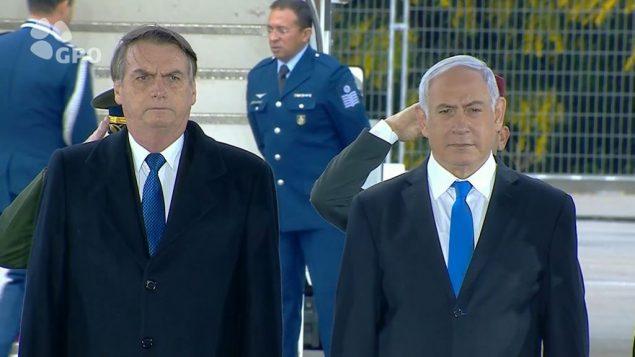الرئيس البرازيلي جايير بولسونارو، الى جانب رئيس الوزراء بنيامين نتنياهو، بعد وصوله مطار بن غوريون لأول زيارة رسمية له لإسرائيل، 31 مارس 2019 (GPO video screen capture)