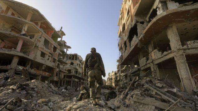 صورة توضيحية: قوات النظام السوري تسير في شارع مدمر عند مدخل مخيم اليرموك للاجئين الفلسطيني في الضواحي اجلنوبية لدمشق في 21 مايو، 2018 بعد أن أعلن الجيش السوري سيطرته الكاملة في العاصمة وضواحيها لأول مرة منذ عام 2012، بعد طرد تنظيم 'الدولة الإسلامية'. (AFP PHOTO / LOUAI BESHARA)