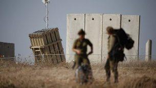 جنود إسرائيليون يسيرون بالقرب من منظومة 'القبة الحديدية' الدفاعية المصممة لاعتراض وتدمير صواريخ قصيرة المدى وقذائف هاون في 9 أغسطس، 2018. (AFP PHOTO / Jack GUEZ)