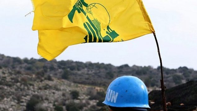 تظهر صورة مأخوذة من قرية ميس الجبل بجنوب لبنان في 16 ديسمبر 2018، جنديا من قوات الأمم المتحدة المؤقتة في لبنان (يونيفيل) يراقب الحدود بين لبنان وإسرائيل. على يمينه علم جماعة حزب الله الشيعية. (Mahmoud Zayyat/AFP)
