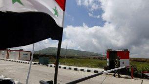 عنصر من قوى الأمن السورية يسير بالقرب من نقطة حدودية مع إسرائيل في مدينة القنيطرة السورية في هضبة الجولان، 26 مارس، 2019.  (Louai Beshara/AFP)