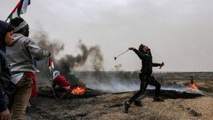 متظاهر فلسطيني يستخدم مقلاعا لإلقاء الحجارة على القوات الإسرائيلية خلال اشتباكات في مظاهرة على طول الحدود مع إسرائيل في ملقا شرق مدينة غزة في 30 مارس 2019. (Mahmud Hams/AFP)