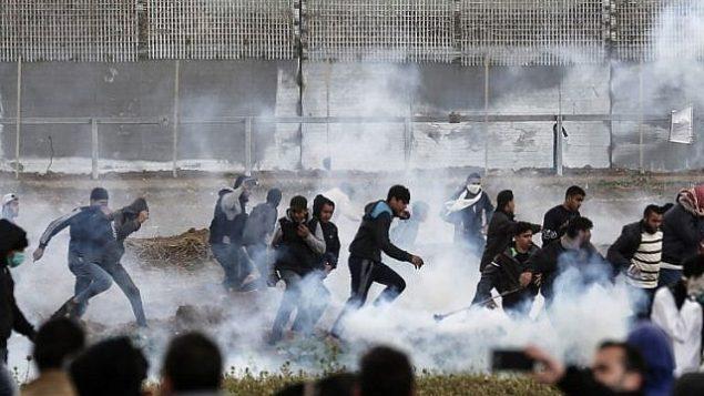 المتظاهرون الفلسطينيون يركضون للاحتماء من عبوات الغاز المسيل للدموع التي أطلقتها القوات الإسرائيلية خلال الاشتباكات وسط مظاهرة حاشدة احتفالا بالذكرى السنوية الأولى لاحتجاجات مسيرة العودة، بالقرب من الحدود مع إسرائيل شرق مدينة غزة في 30 مارس 2019. (Mahmud Hams/AFP)