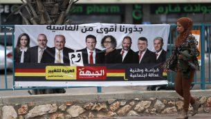 سيدة عربية اسرائيلية تمر امام لافتة انتخابية تظهر مرشحين عرب اسرائيليين في كفر مندا (AHMAD GHARABLI / AFP)