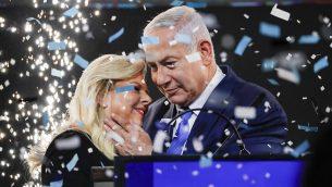 يحتضن رئيس الوزراء بنيامين نتنياهو زوجته سارة وسط وريقات الإحتفال أثناء خطاب النصر أمام أنصار حزب الليكود في تل أبيب بعد انتخابات 9 أبريل 2019. (Thomas Coex/AFP)