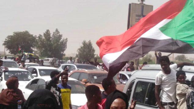 متظاهرون سودانيون يسيرون باتجاه مقر الجيش خلال تظاهرة في العاصمة الخرطوم، 11 أبريل، 2019.  (Photo by - / AFP)