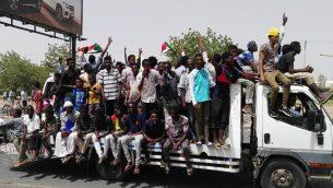 رجال سودانيون يحتفلون خلال مظاهرات في الخرطوم، 11 ابريل 2019 (AFP)