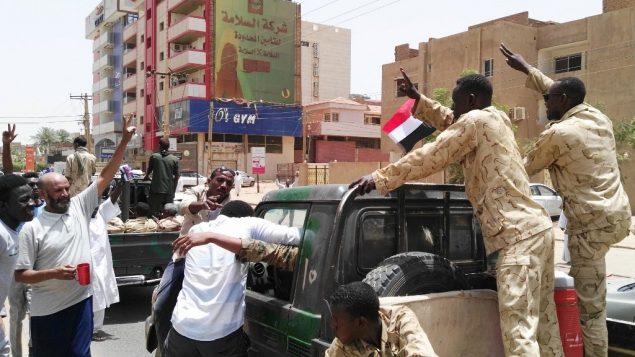 سودانيون وعناصر من قوى الأمن يشيرون بعلامة النصر في 11 أبريل، في العاصمة الخرطوم.  (Photo by - / AFP)