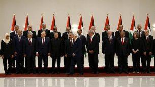 رئيس السلطة الفلسطينية محمود عباس (السادس من اليمين) يسير مبتعدا بعد التقاط صورة جماعية لأعضاء الحكومة الفلسطينية الجديدة في مدينة رام الله بالضفة الغربية، 13 أبريل، 2019. (Abbas Momani/AFP)