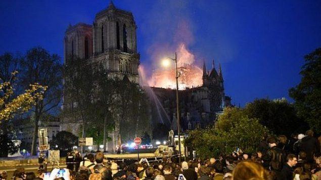 اشخاص يشاهدون الدخان والنيران تتصاعد من كاتدرائية نوتردام في باريس، 15 ابريل 2019 (ERIC FEFERBERG / AFP)