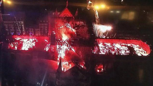 صورة التقطت لشاشة تلفزيون تظهر تصوير جوي لكاتدرائية نوتردام مع السنة لهب تتصاعد منها، في العاصمة الفرنسية باريس، 15 ابريل 2019 (AFP)