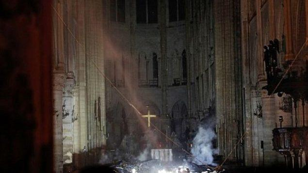 الدخان امام صليب المذبح في كاتدرائية نوتردام في باريس، 15 ابريل 2019 (PHILIPPE WOJAZER / POOL / AFP)