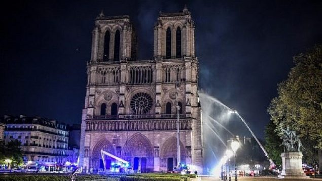 رجا اطفاء يتجمعون عند واجهة كاتدرائية نوتردام في باريس، بينما تنتشر النيران في سطح المبنى، 15 ابريل 2019 (STEPHANE DE SAKUTIN / AFP)