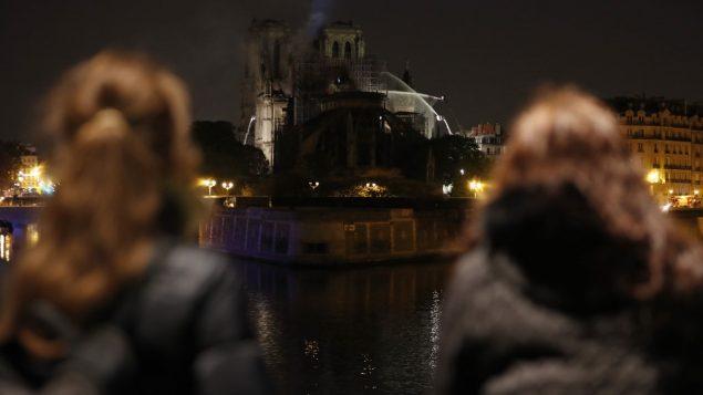 اشخاص يشاهدون الدخان والنيران تتصاعد من كاتدرائية نوتردام في باريس، 16 ابريل 2019 (Zakaria ABDELKAFI / AFP)