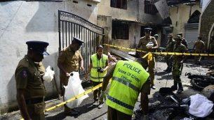 عناصر امن وعناصر شرطة يفحصون الحطام خارج كنيسة بعد تفجير في باتيكالوا، شرق سريلانكا، 21 ابريل 2019 (LAKRUWAN WANNIARACHCHI / AFP)