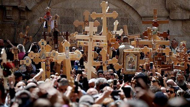 المسيحيون الأرثوذكس يدخلون بصلبان خشبية في كنيسة القيامة أثناء احتفالهم بيوم الجمعة العظيمة في موكب في طريق الآلام في البلدة القديمة في القدس، في 26 أبريل 2019. (Thomas Coex/AFP)