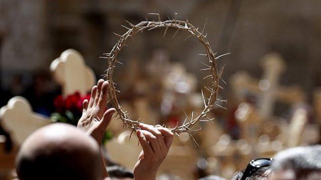 المسيحيون الأرثوذكسيون يلوحون بتاج الشوك في كنيسة القيامة بعد احتفالهم بيوم الجمعة العظيمة في موكب على طريق الآلام في المدينة القديمة في القدس، في 26 أبريل 2019. (Thomas Coex/AFP)