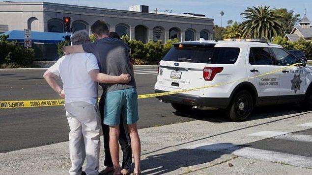 اشخاص امام شريط ساحة جريمة مقابل كنيس تعرض لإطلاق نار في سان دييغو، 27 ابريل 2019 (SANDY HUFFAKER / AFP)