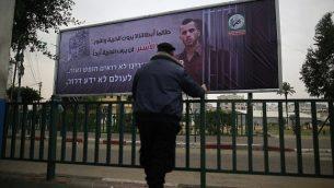 """شرطي فلسطيني تابع لحركة """"حماس"""" ينظر إلى لافتة تحمل صورة الجندي الإسرائيلي القتيل أورون شاؤول في مدينة غزة، 29 ديسمبر، 2017، كُتب عليها بالعربية: """"طالما أبطالنا لا يرون الحرية والنور، هذا الأسير لن يرى الحرية أبدا"""".  (AFP PHOTO / MOHAMMED ABED)"""