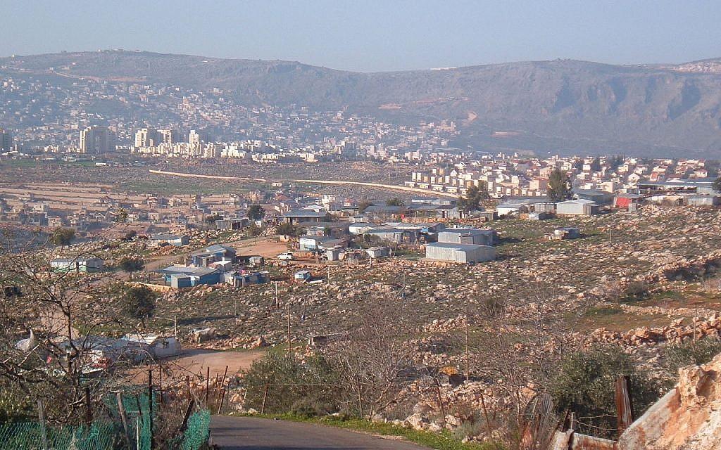 صورة لقرية عرب النعيم البدوية في المقدمة، مع مدينة كرمئيل في الخلفية، 25 فبراير، 2006.  (Public Domain/Wikipedia)