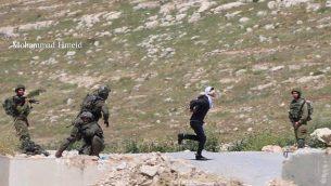 جندي اسرائيلي يلاحق مشتبه به فلسطيني اقناء محاولته القرار في قرية تقوع في الضفة الغربية، 18 ابريل 2019 (Mohammad Hmeid)