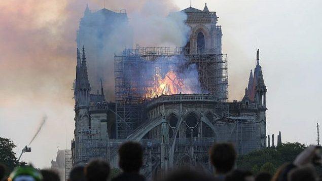 اشخاص يشاهدون الدخان والنيران تتصاعد من كاتدرائية نوتردام في باريس، 15 ابريل 2019 (AP Photo/Thibault Camus)