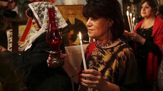 المصلون الأرثوذكس المسيحيون يحملون شموعا خلال حفل عيد الفصح في كنيسة القديس بورفيريوس في مدينة غزة، السبت، 15 أبريل، 2017. (AP Photo / Adel Hana)