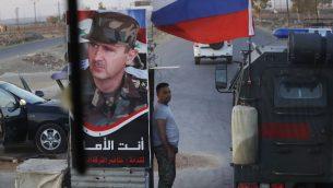 جندي سوري في حاجز اثناء مرور مركبة عسكرية روسية، بالقرب من قرية المجدية في سوريا، 14 اغسطس 2018 (AP/Sergei Grits)