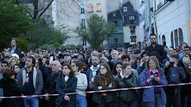 اشخاص يشاهدون الدخان والنيران تتصاعد من كاتدرائية نوتردام في باريس، 15 ابريل 2019 (AP/Michel Euler)