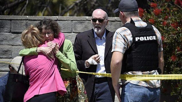 اشخاص يتحدثون مع شرطي امام كنيس تعرض لإطلاق نار في سان دييغو، 27 ابريل 2019 (AP/Denis Poroy)