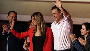 رئيس الوزراء الإسباني ومرشح الحزب الاشتراكي، بدرو شانشيز، يقف مع زوجته ماريا بيغونا غومير لتحية المناصرين الذين اجتمعوا في مقر الحزب في مدريد بانتظار نتائج الانتخابات العامة، الأحد، 29 أبريل، 2019.  (AP Photo/Andrea Comas)