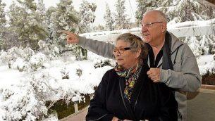 من الأرشيف: رئيس الدولة رؤوفين ريفلين وزوجته نحاما يتفرجان على حديقة مغاطة بالثلج في مقر إقامة الرئيس في القدس بعد عاصفة ثلجية في العاصمة، فبراير 2015. (Haim Zach/GPO)