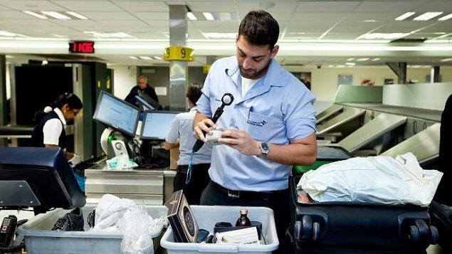 موظف في مطار بن غوريون يفتش امتعة المسافرين، 2014 (Moshe Shai/FLASH90)