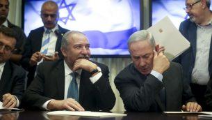 رئيس الوزراء بنيامين نتنياهو ورئيس حزب 'يسرائيل بيتينو' افيغادور ليبرمان يوقعان على اتفاق ائتلافي في الكنيست، 25 مايو 2016 (Yonatan Sindel/FLASH90)