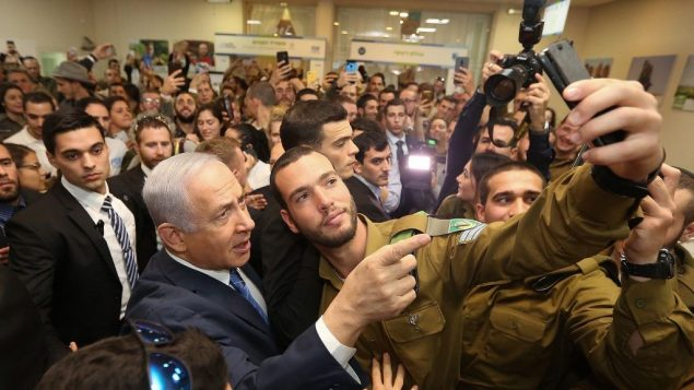 رئيس الوزراء بنيامين نتنياهو يلتقط صورة مع جندي خلال حدث للجنود الوحيدين في تل ابيب، 24 يناير 2019 (Marc Israel Sellem/Pool/Flash90)